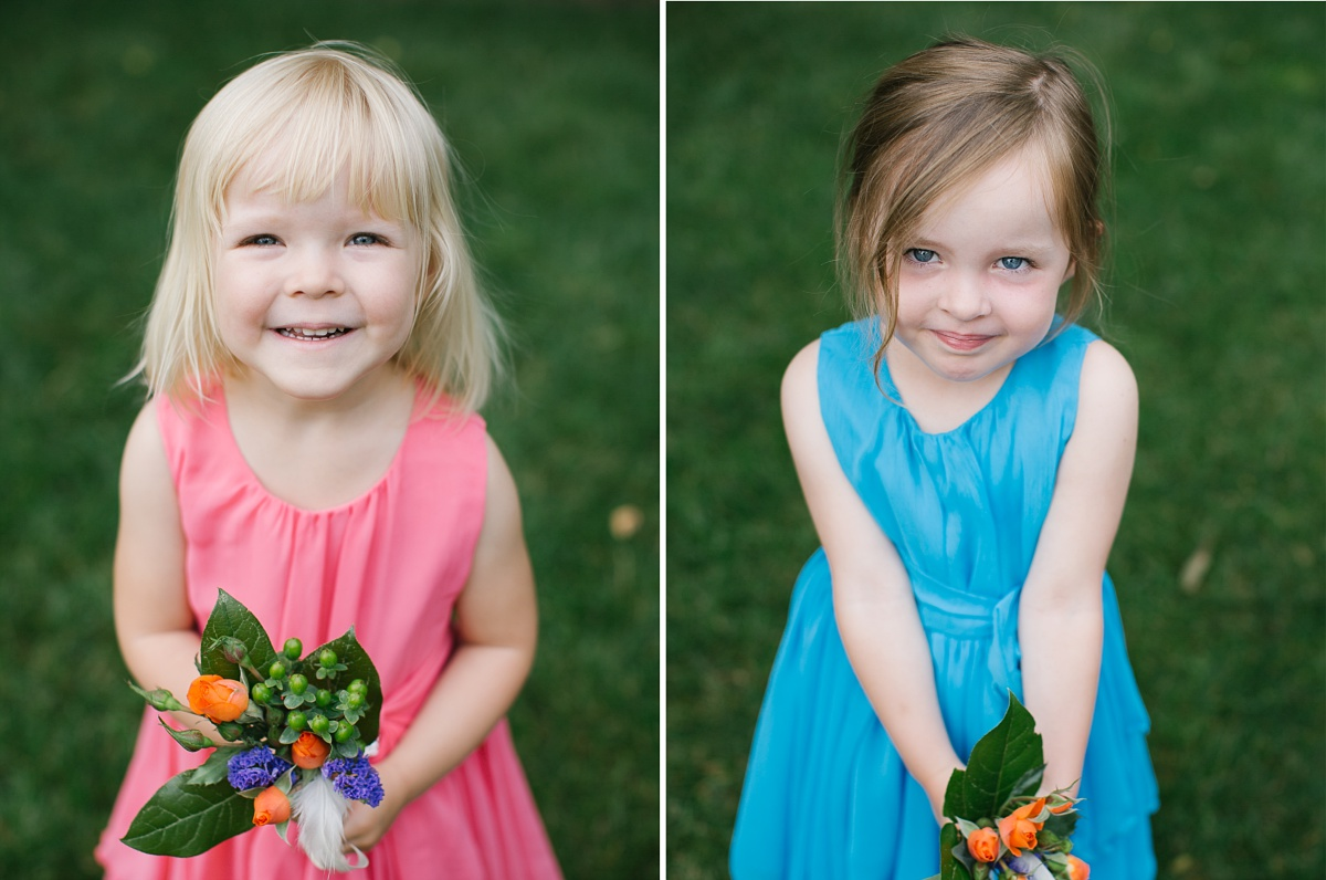 Young girls in cute pink and blue dresses smile for the wedding photos