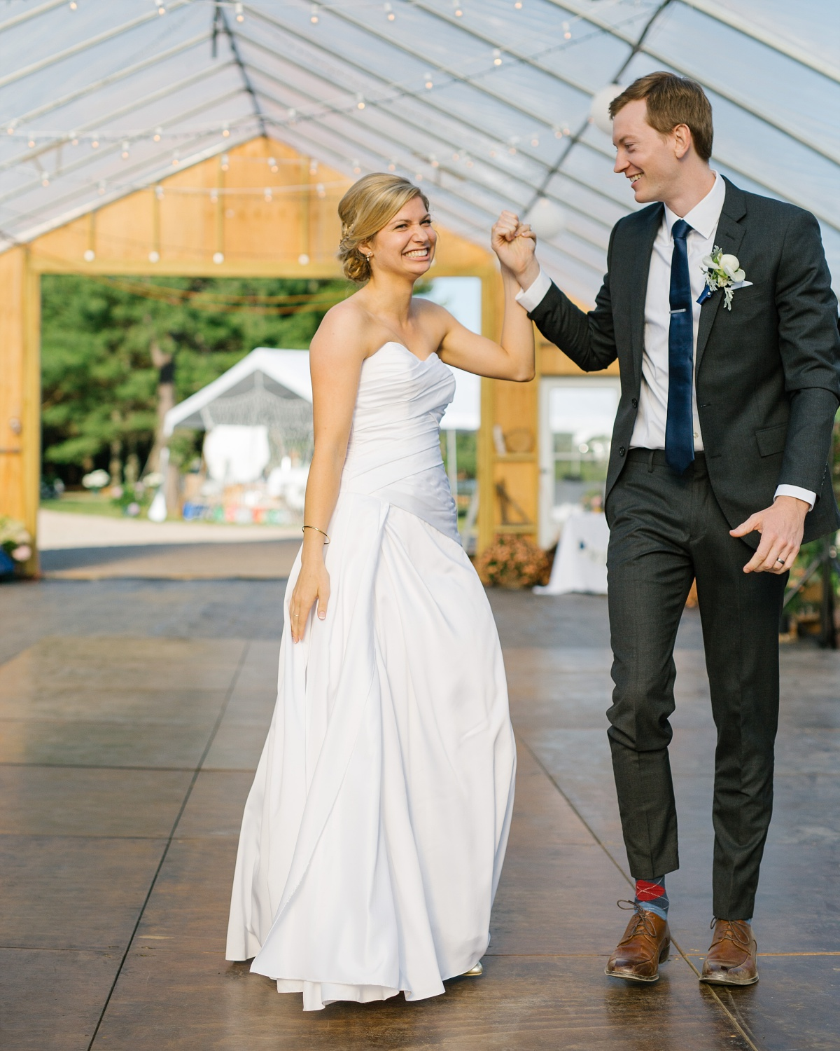 Bride and groom smile and dance at family barn wedding in Rhode Island