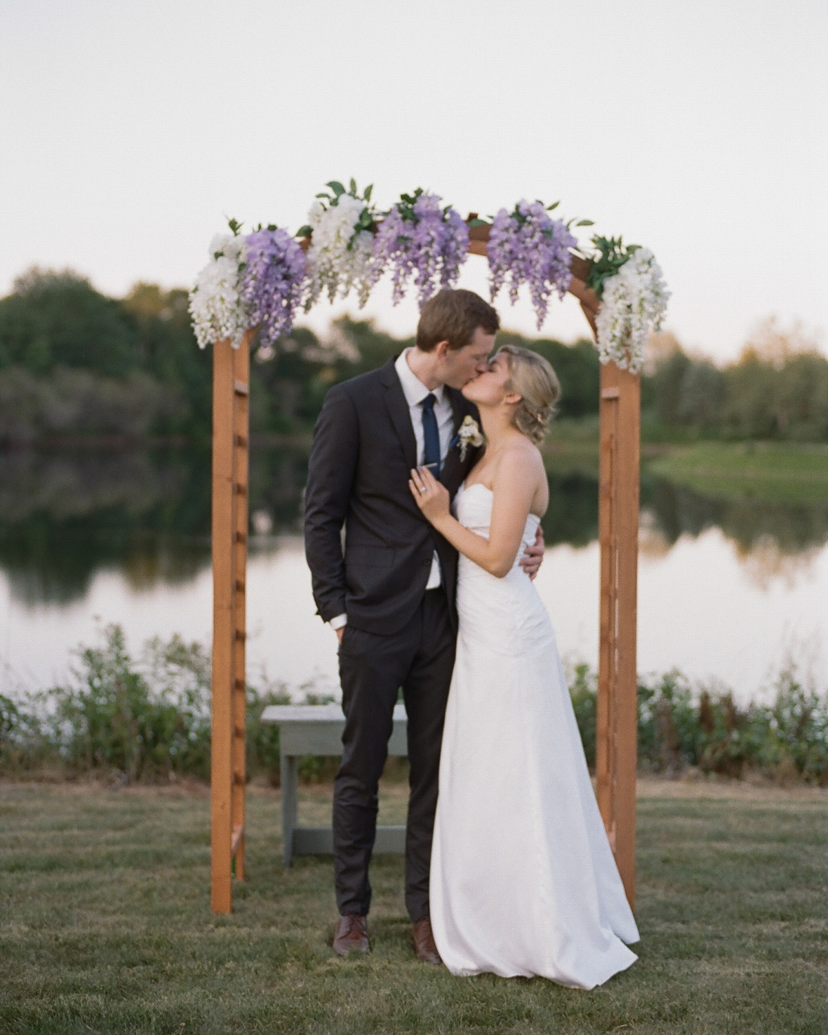Bride and groom kiss underneath lilacs by the pond