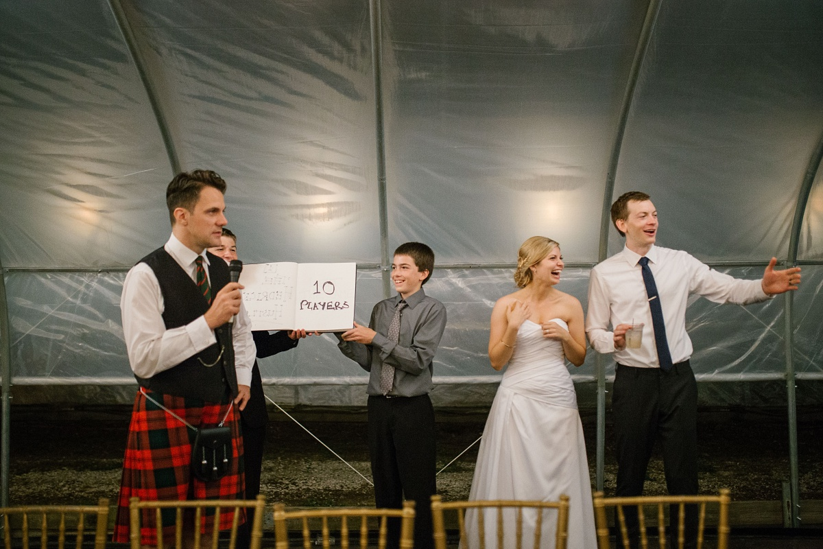 Guests enjoy wedding game as man in a kilt narrates