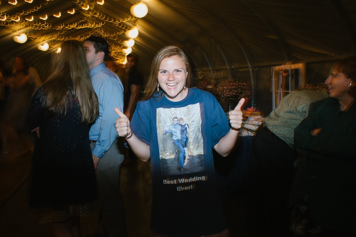 "Woman gives a thumbs up and wears a ""Best Wedding Ever!"" shirt with a wedding picture on it"