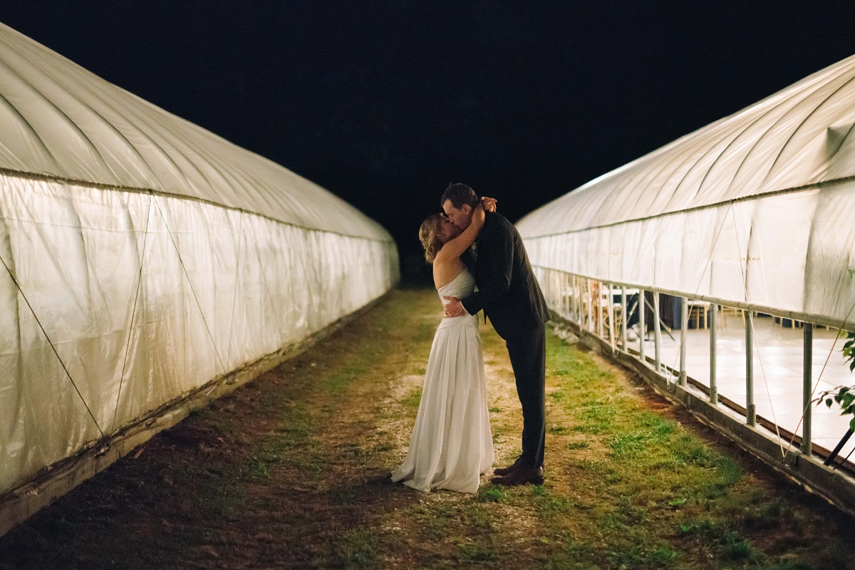 Bride and groom kiss against the pitch black sky at their family farm wedding