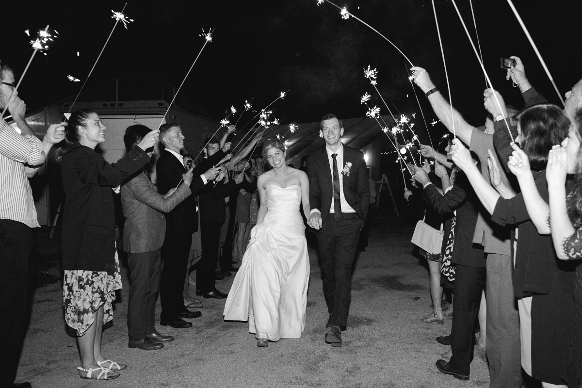 Bride and groom leave for the honeymoon through tunnel of sparklers
