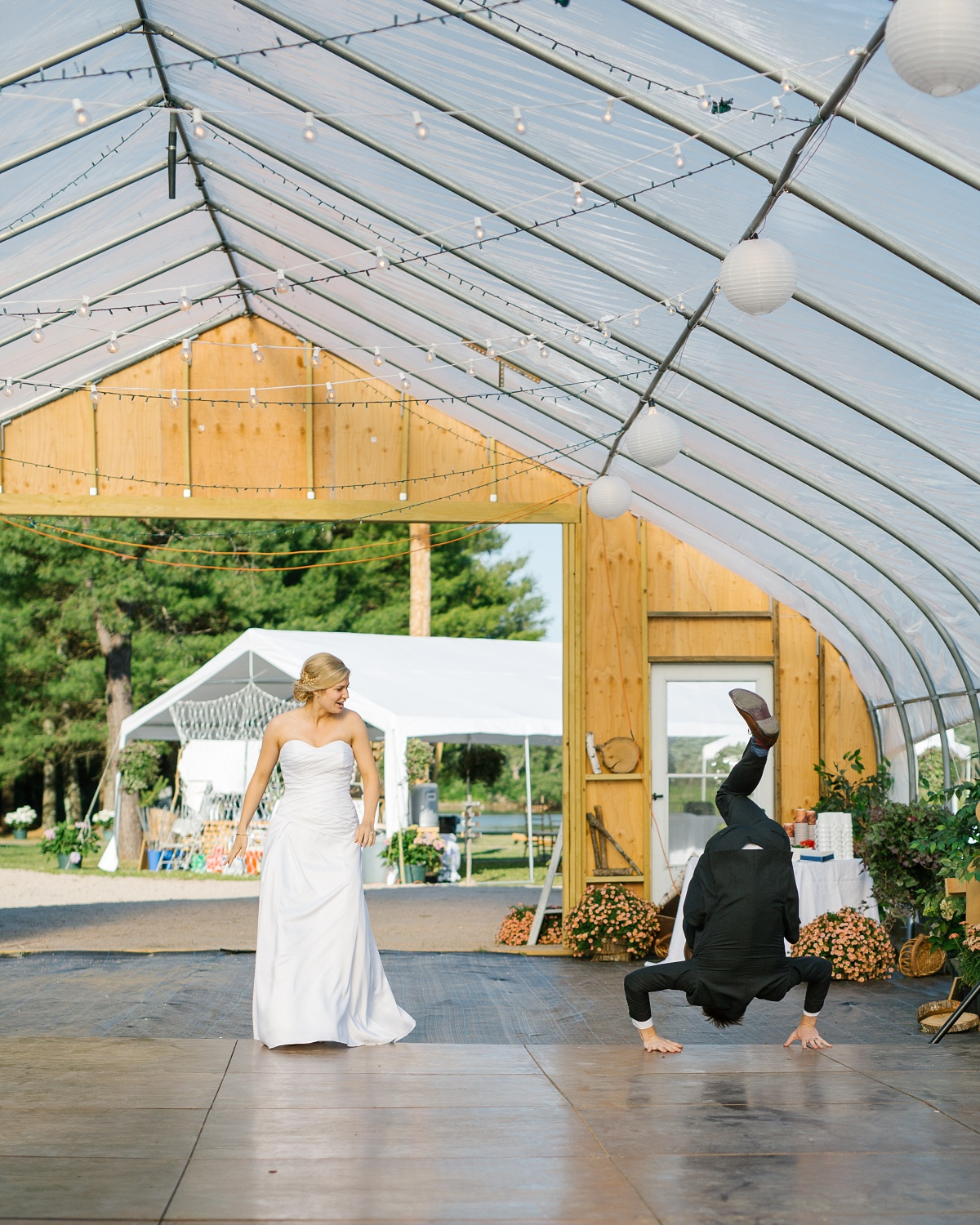 Groom break dances at outdoor barn wedding