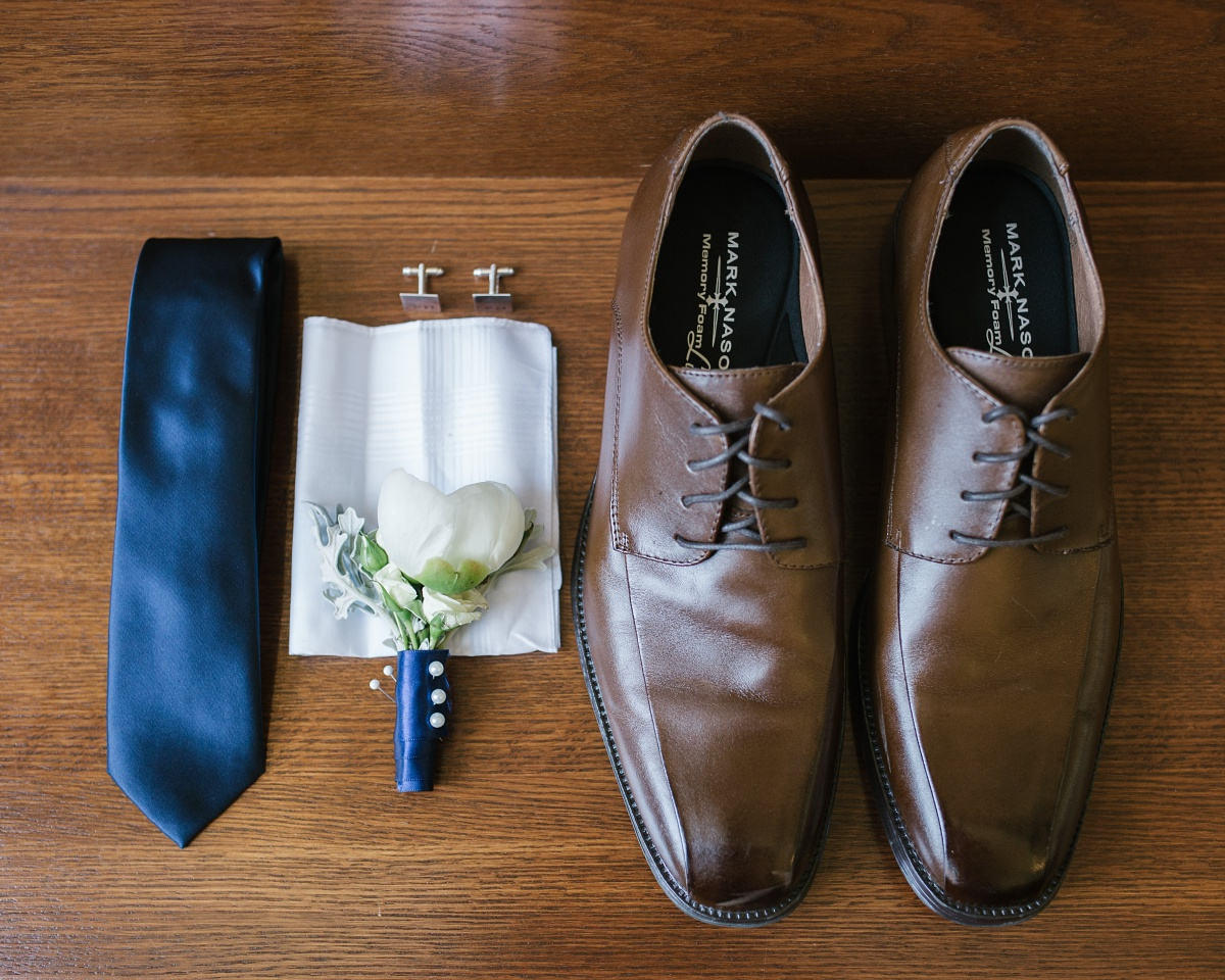 Detailed shot of groom's shoes, tie, and accessories