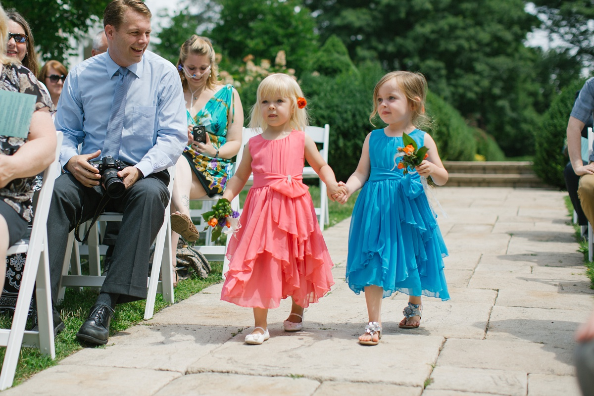 Two adorable toddler flower girls walk down the aisle