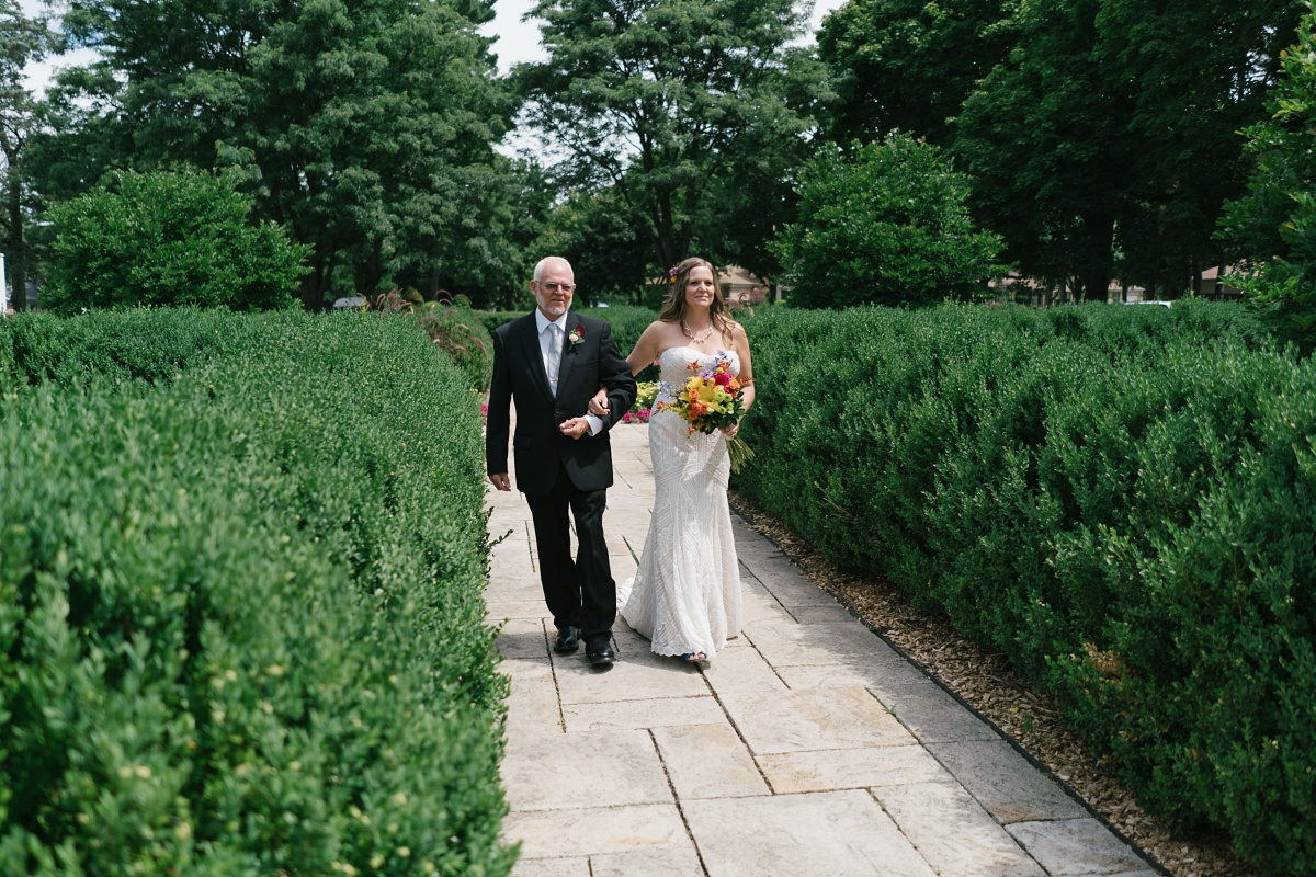 Bride and her father walk down the aisle through the beautiful Hurley Gardens
