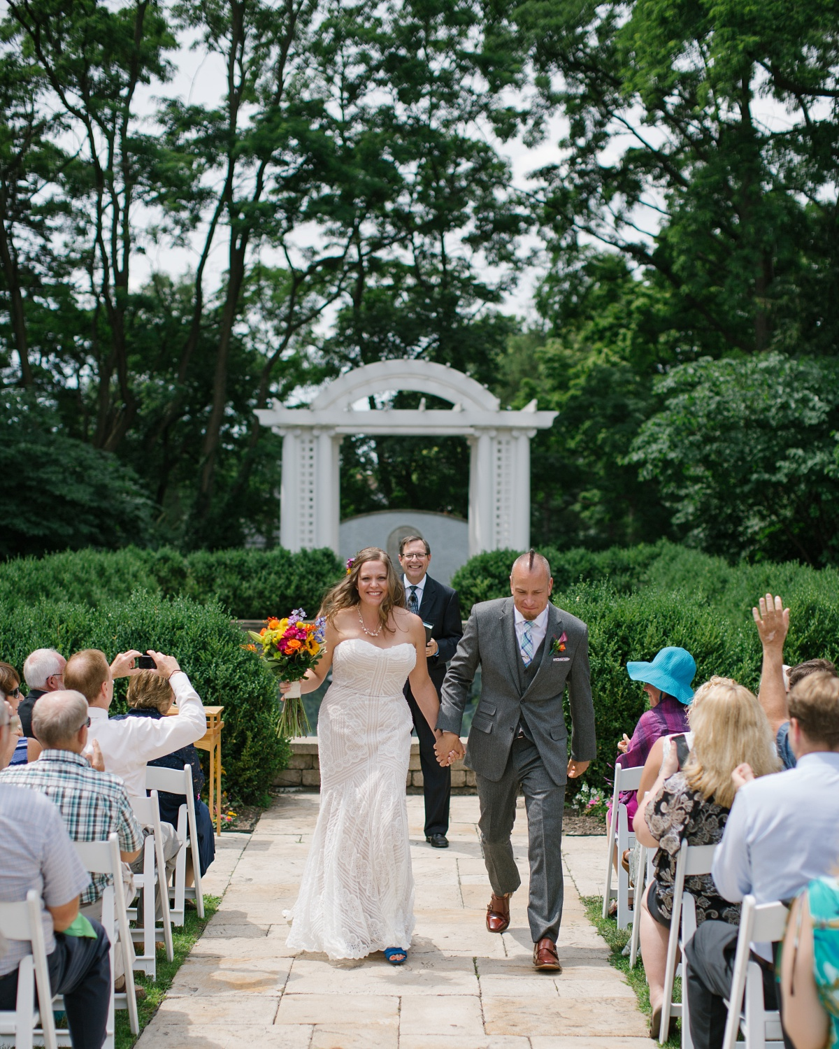 Happy bride and groom walk out of the ceremony hand-in-hand