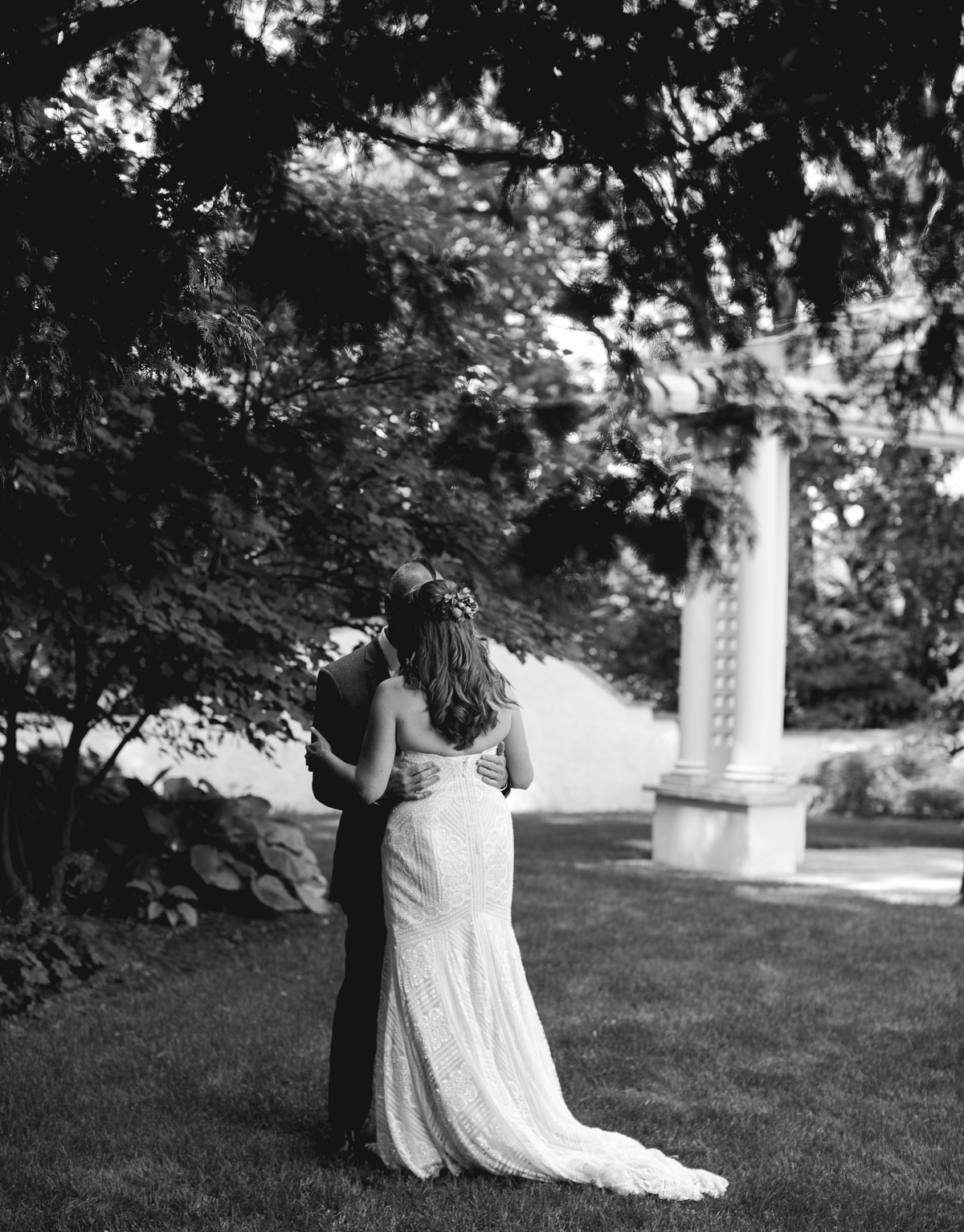 bride and groom embrace in a garden before the wedding ceremony