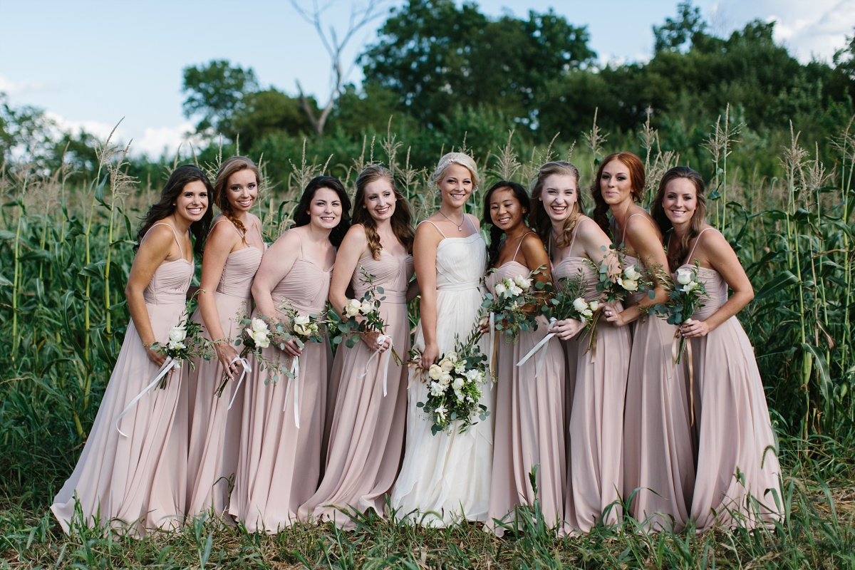 Bridal party with neutral colored dresses pictured against greenery