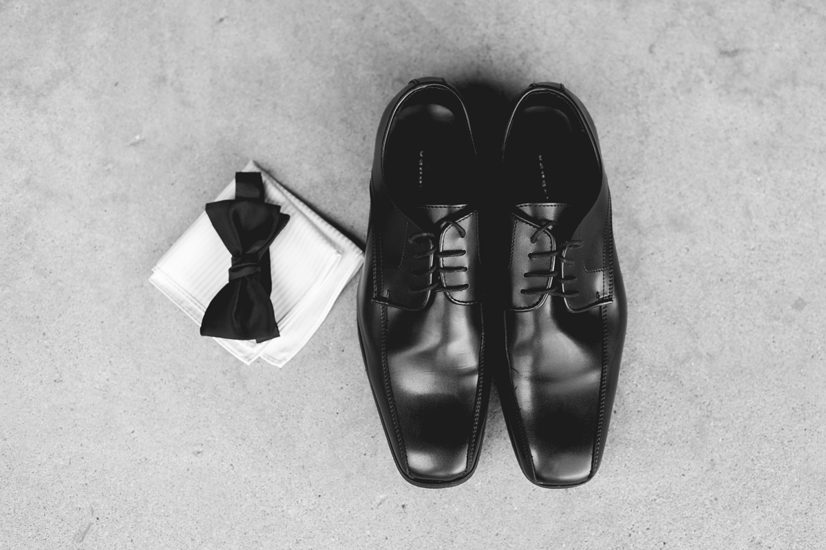 Detailed shot of groom's black shoes, bow tie, and handkerchief.