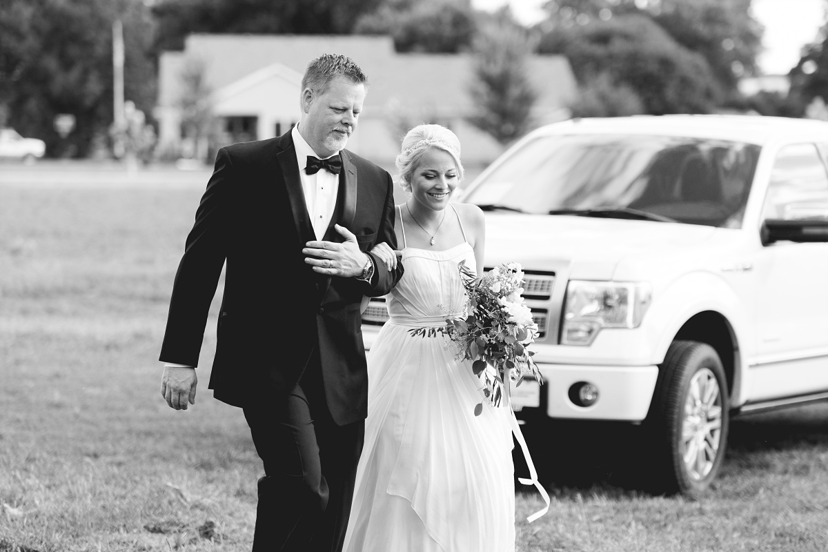 Father walks daughter down the aisle at barn wedding