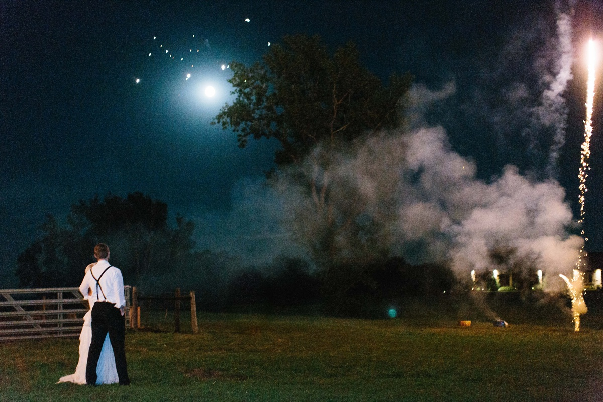 Bride and groom look at the moon and fireworks at farm wedding