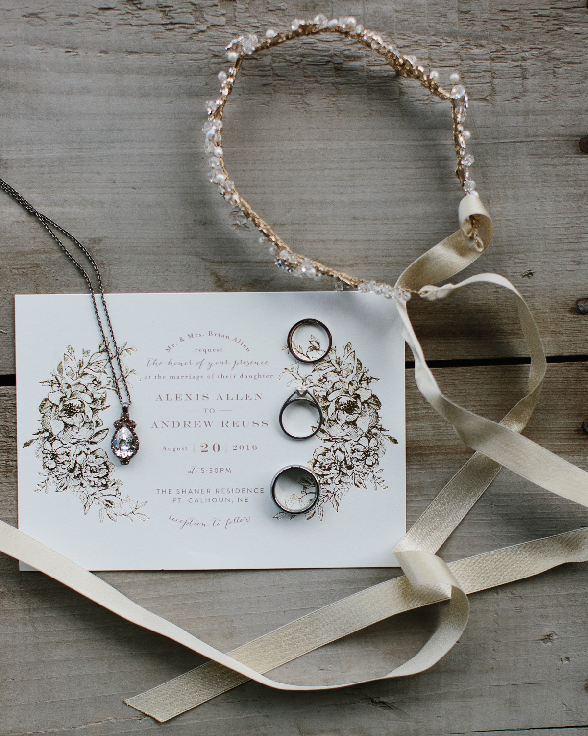 wedding invitation, wedding rings, and jewelry displayed together