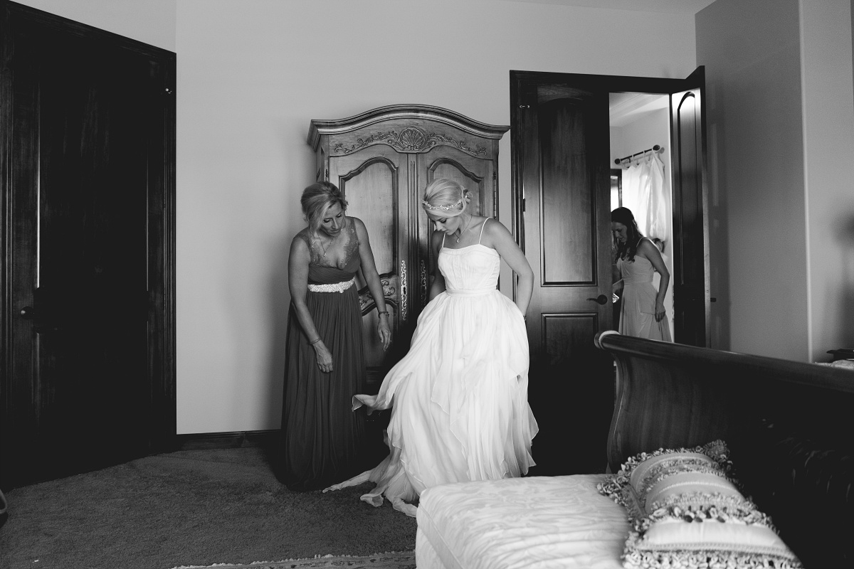 Black and white photo of bride putting on her wedding dress