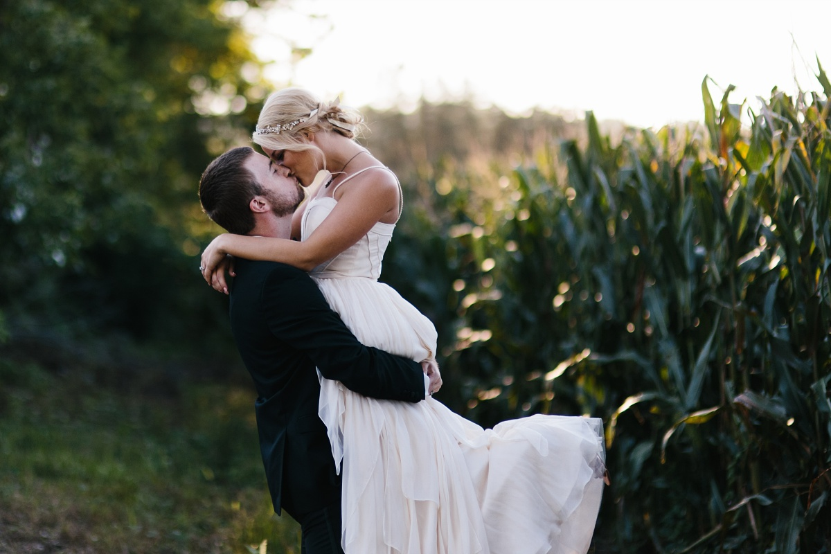 Bride and groom kiss in a corn field