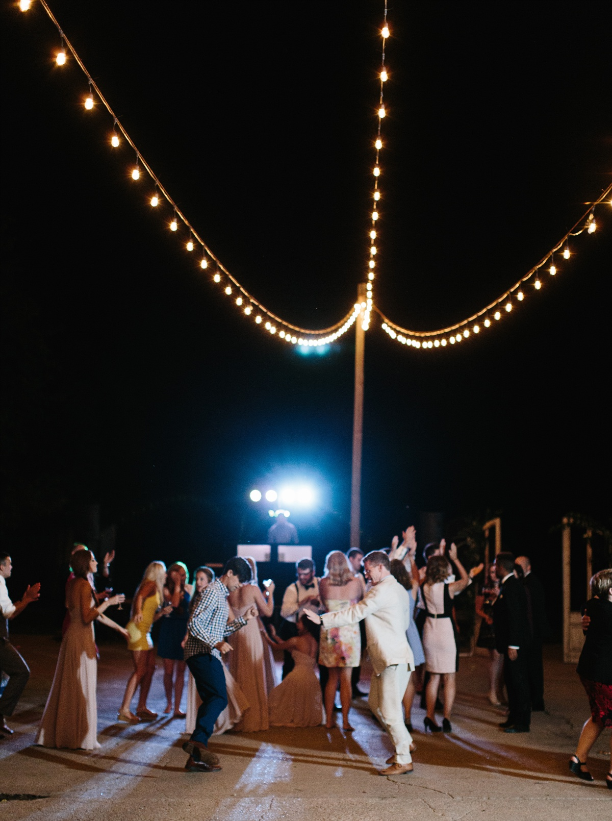 Wedding guests dance in the nighttime outdoor reception