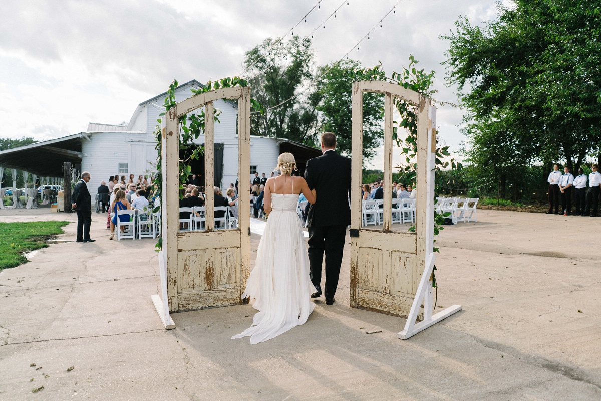 shot behind the bride and her father as they walk down the aisle of outdoor wedding