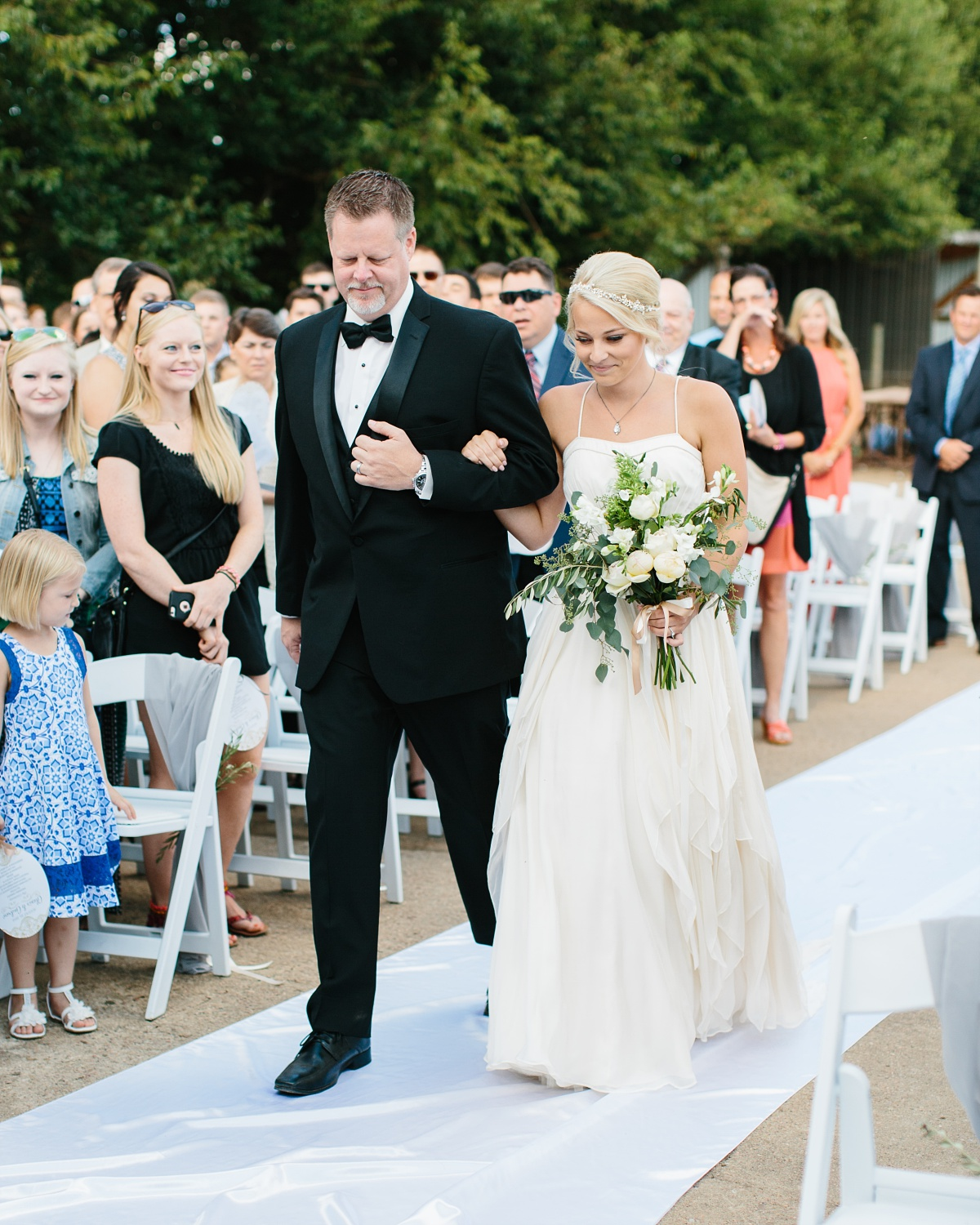 Dad walks his daughter down the aisle of outdoor wedding