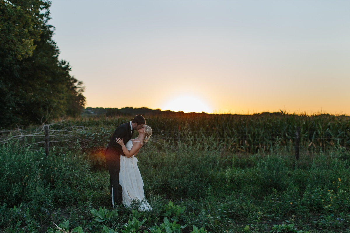 Bride and groom kiss at sunset in a cornfield