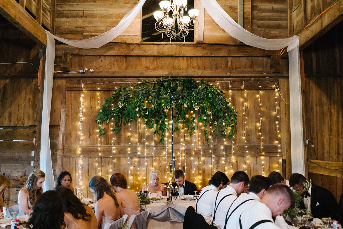 Hanging lights above the bridal party table in rustic barn wedding